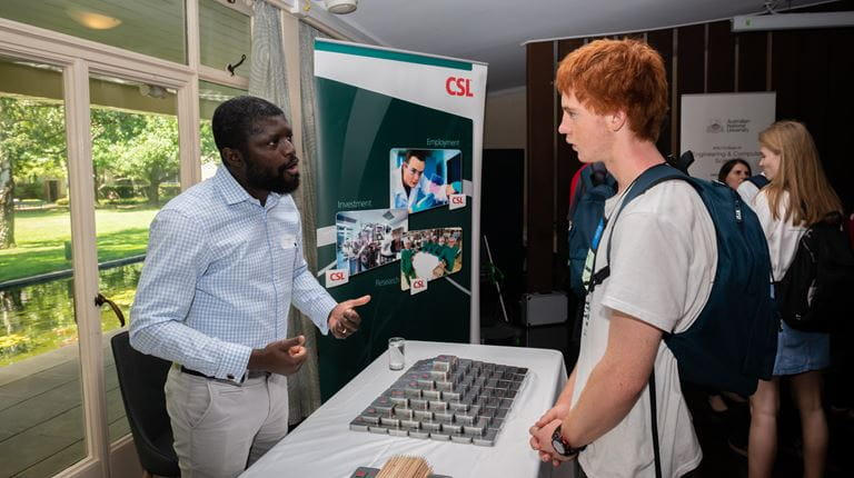 Image of CSL Scientist Innocent Bekard speaking to a student participating in the 2019 NYSF sessions