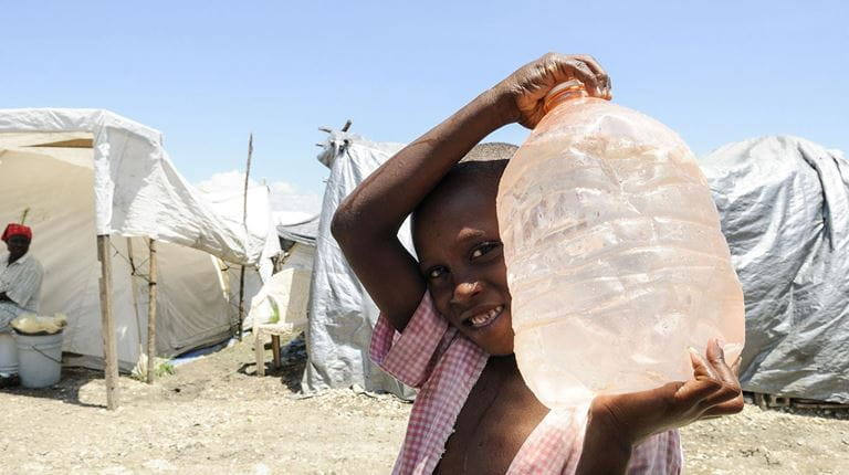 Disaster relief young child holding large water bottle in a refuge camp